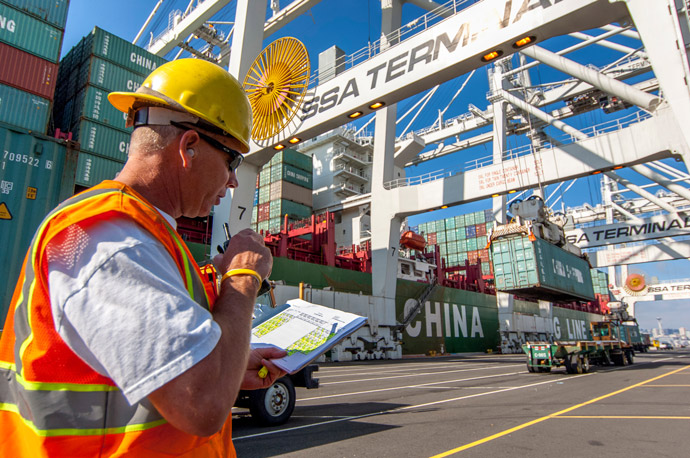 An operator works at Terminal 5 as cargo containers are stacked in the background.