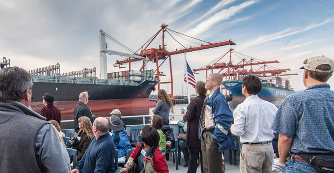 Community members sit and stand on a dock while looking at boats and shipping containers at Terminal 5.